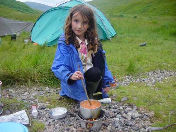 A young girl stirring beans in a STORM CookKit pot